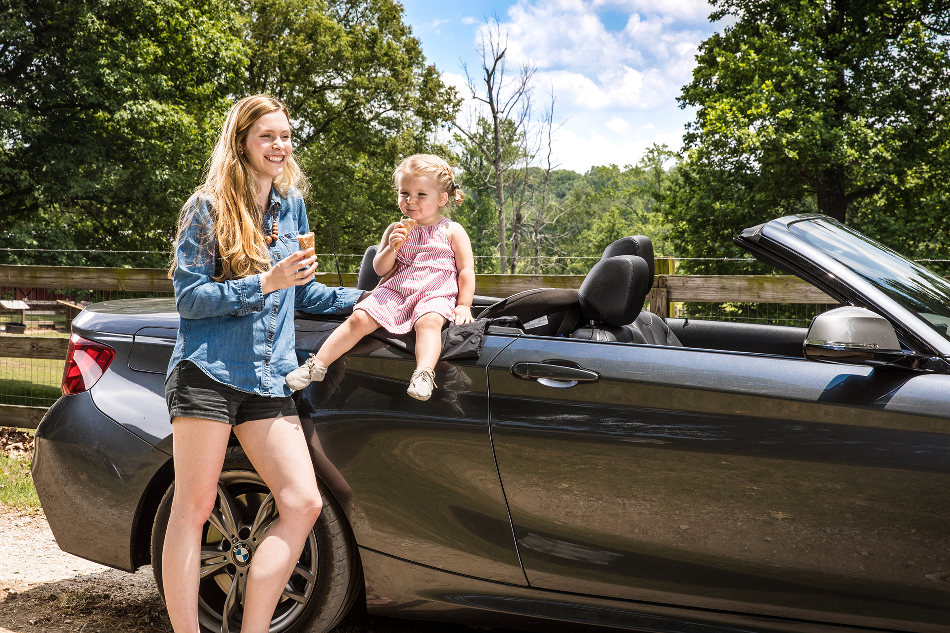 Mom and daughter eat icecream beside their subscription car